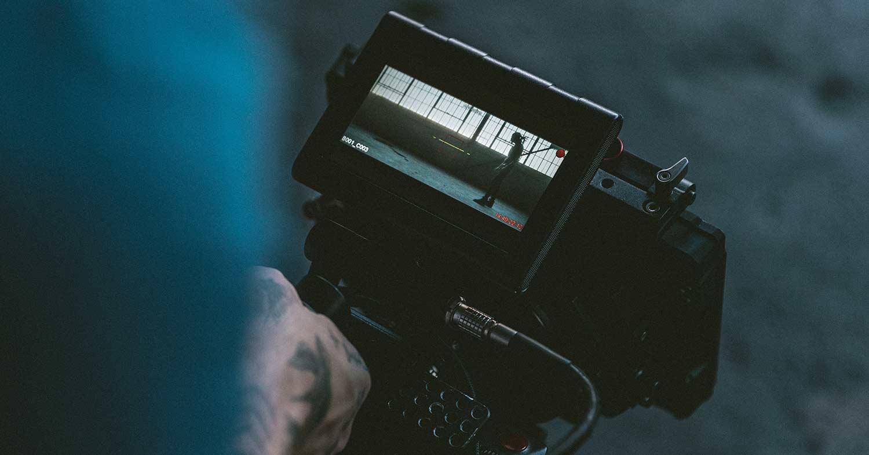 3 video marketing tricks - man filming on video camera